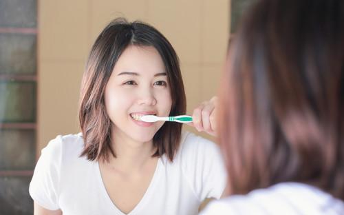 Asian girl brushing teeth