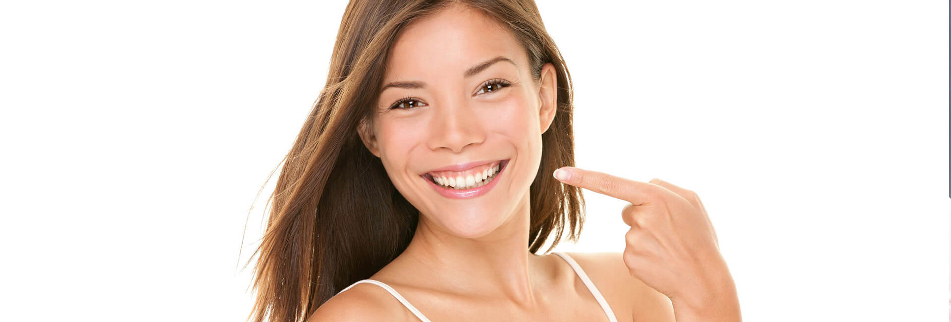 Happy female smiling pointing at her bright white teeth