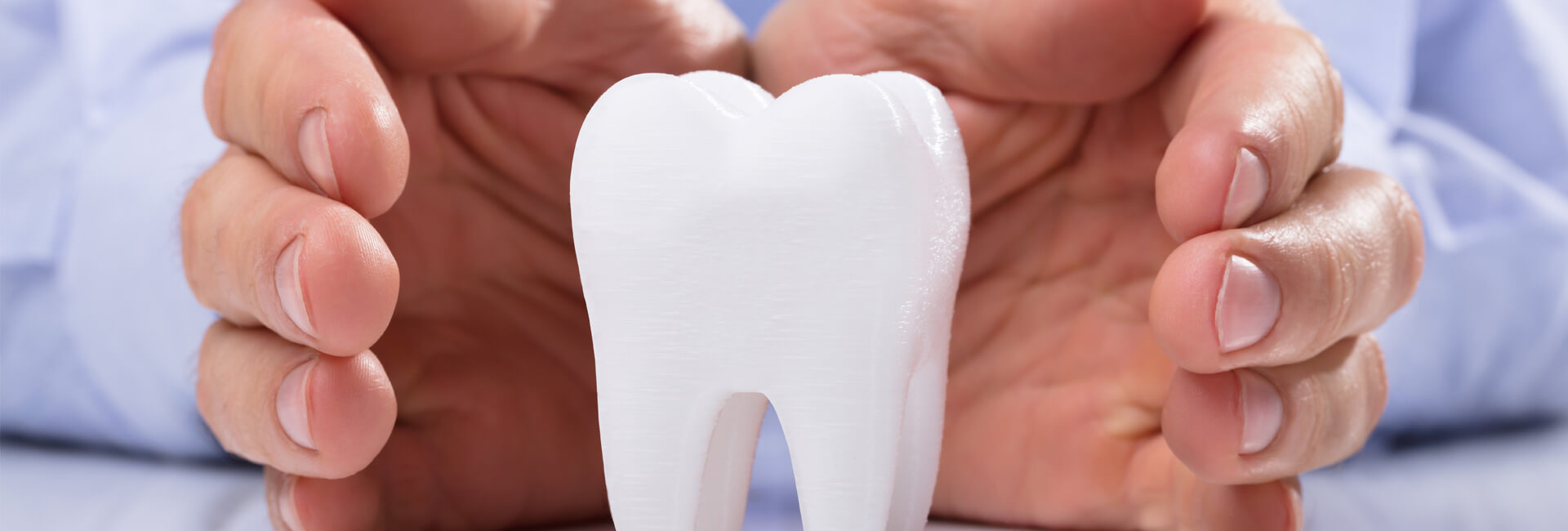 Two hands protecting a tooth structure