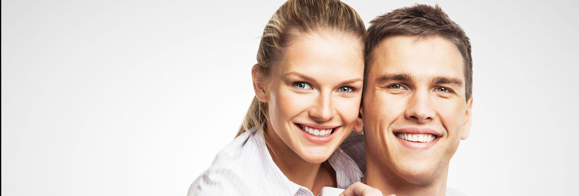 Young couple smiling showing white teeth embracing each other