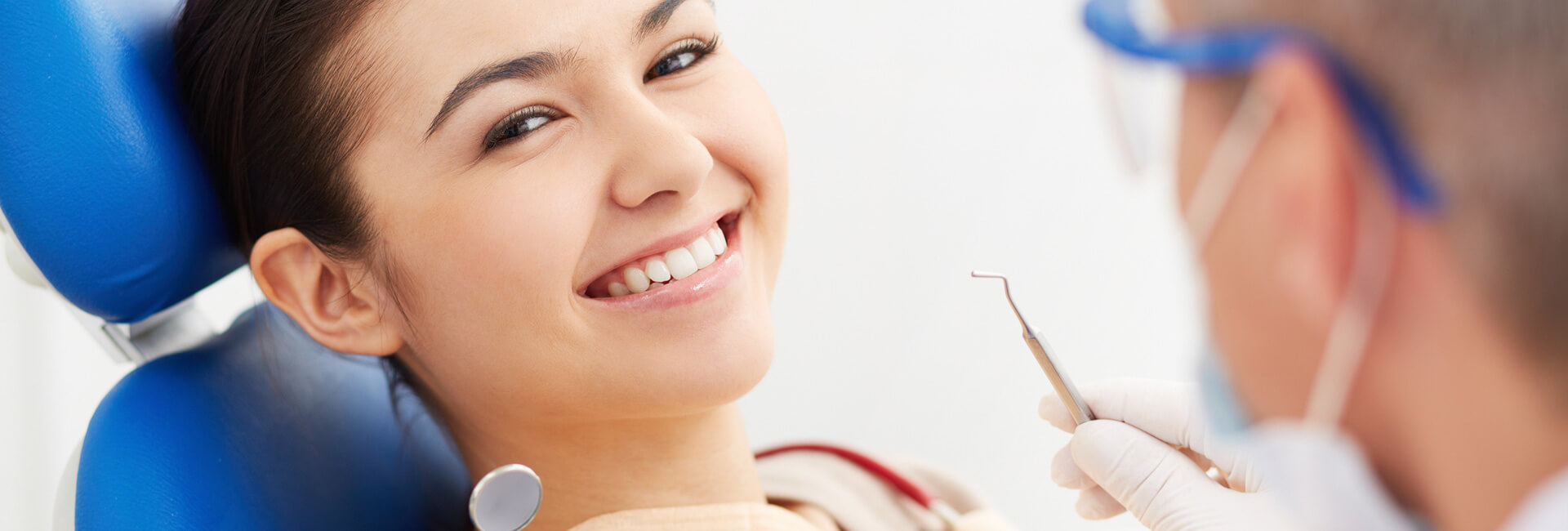 Happy patient smiling seated at dental chair while dentist is holding a dental prosthetic