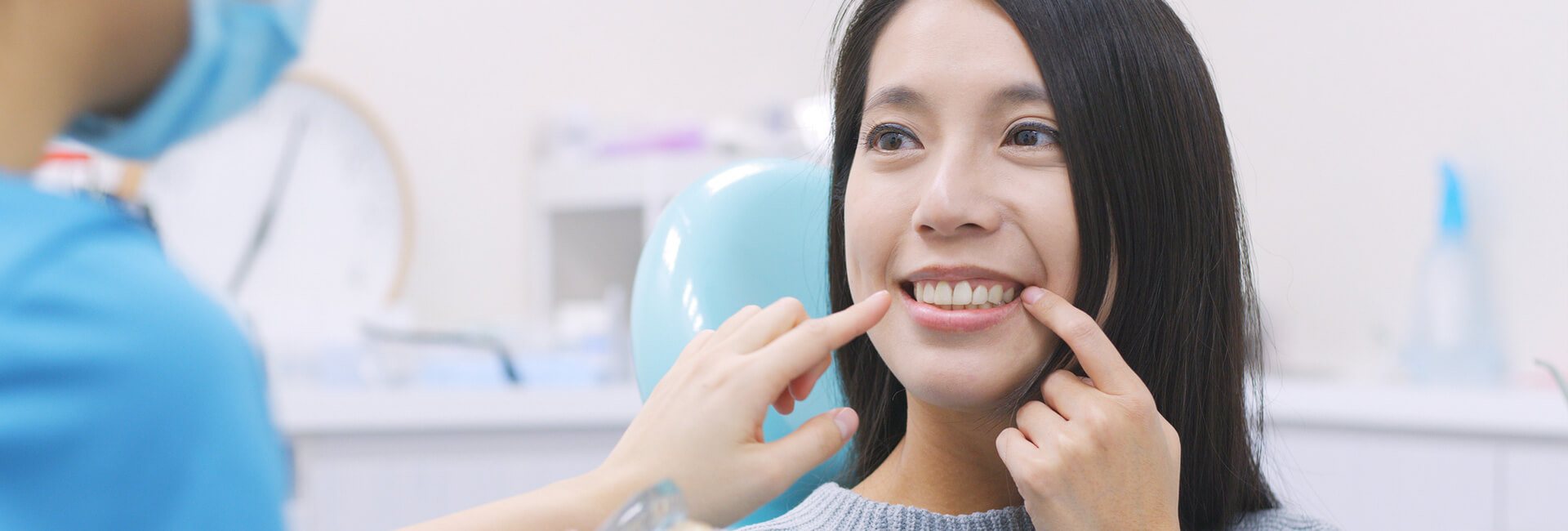 Young woman pointing at her teeth seated on dental chair