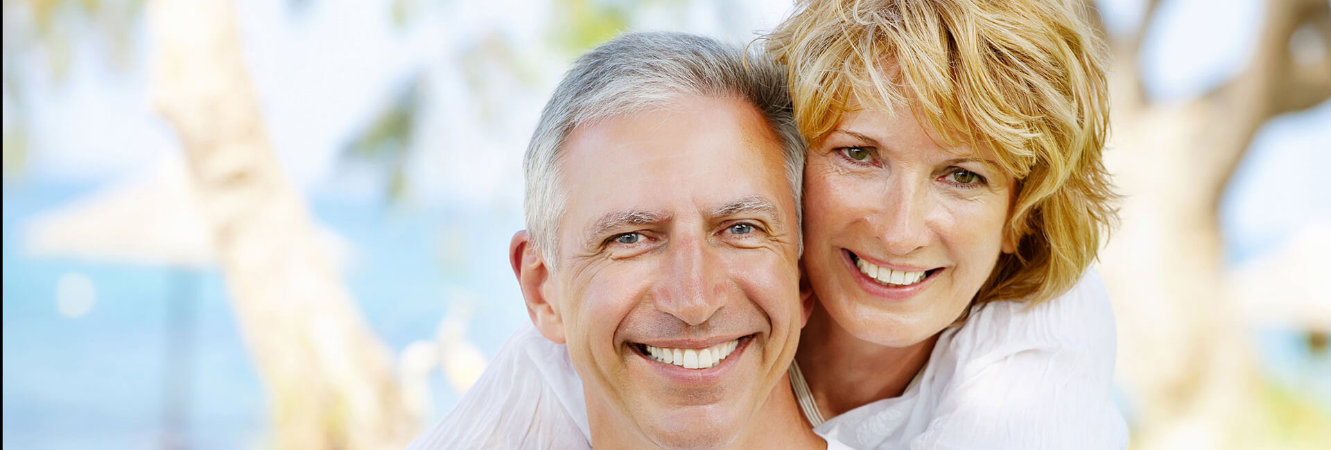 Elderly couple smiling outdoors embracing each other