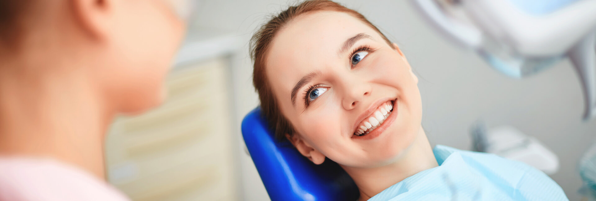Smiling female patient seated on dental chair