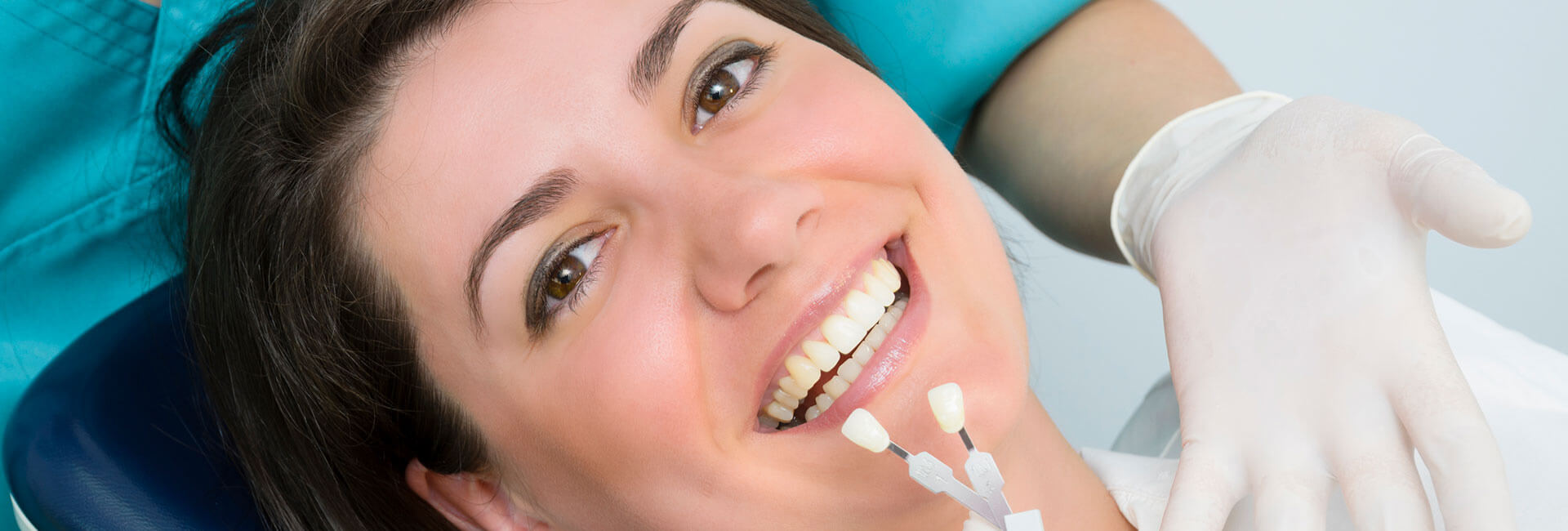 Patient smiling while dentist is comparing a pair of dental prosthetics